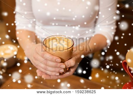 latte art, coffee shop, people and winter concept - close up of hands with butterfly etching in coffee cup over snow