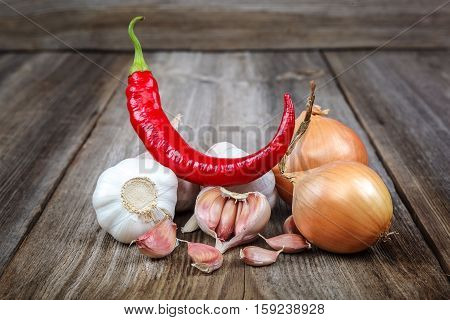 Fresh garlic onion and red hot peppers on wooden background.