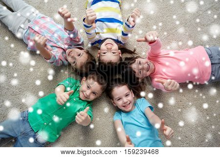 christmas, winter holidays, childhood, friendship and people concept - group of happy smiling little children lying on floor and showing thumbs up over snow