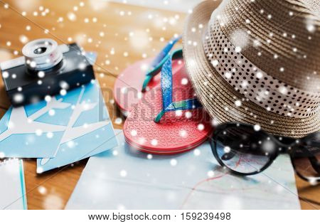 tourism, winter holidays and objects concept - close up of travel map, flip-flops, hat and camera with airplane tickets on wooden table at home