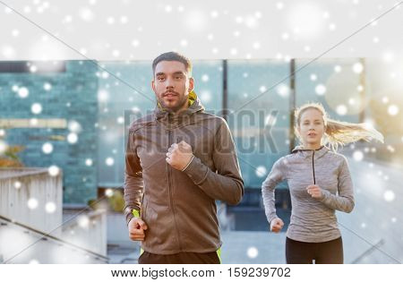 fitness, sport, people, exercising and healthy lifestyle concept - happy couple of sportsmen running upstairs on city stairs over snow