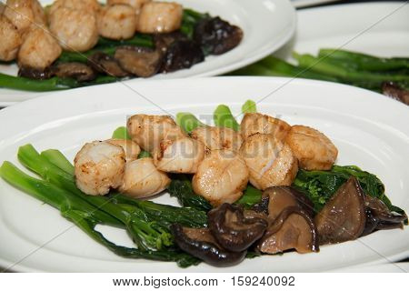 Studio closeup of seared scallops garnished with vegetables presented on a scallop shell.