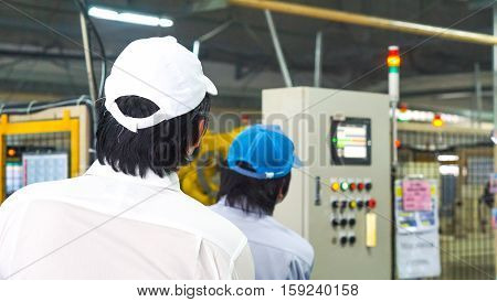 industrial machine and technician concept - Blurred control box unit with asian man technician checking in factory and copyspace