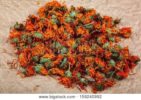Dried calendula flowers on paper background. Medicinal plants.
