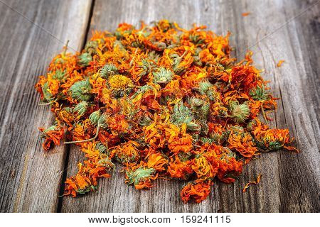 Dried calendula flowers on wooden background. Medicinal plants.