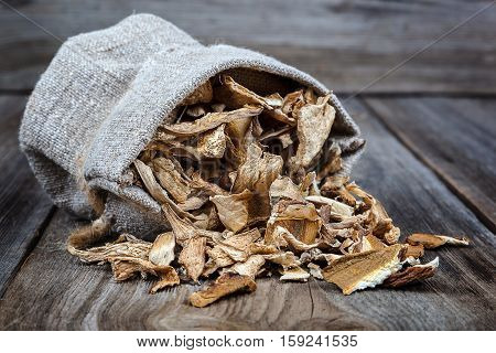 Dried porcini mushrooms in a canvas bag on a wooden background.