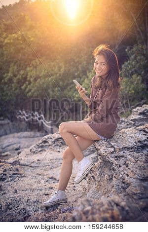 younger asian woman toothy smiling face happiness emotion with smart phone connecting in hand for digital modern lifestyle