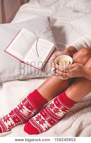 Woman Sitting On A Bed With A Book And Tea