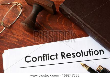 Papers with title conflict resolution on a table.