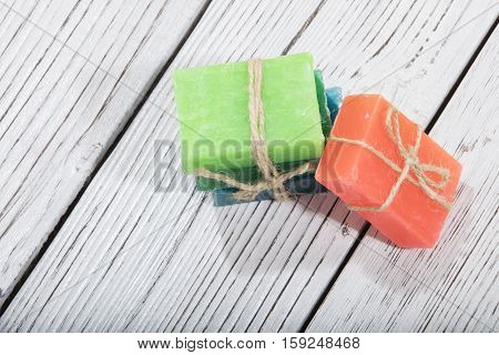 different colorful natural herbal soaps on wooden background
