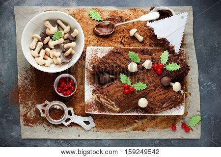 Christmas Bush de Noel - homemade chocolate yule log cake cooking decoration Christmas log holly berries leaves and candy mushrooms Christmas and New Year holiday traditional recipe step by step