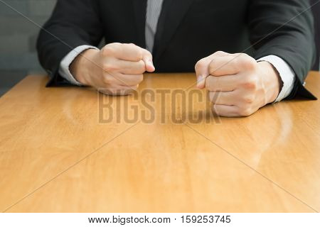 Businessman with clenched fist on the desk at office Angry concept