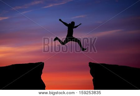 Man jumping across the gap from one rock to cling to the other. Man jumping over rocks with gap on sunset fiery background. Element of design.