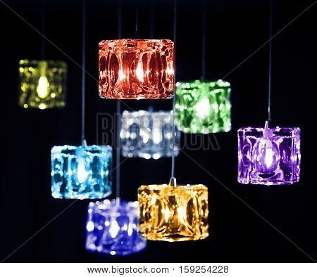 Closeup view of contemporary light fixture on dark background. Small bright colorful lights creating festive and romantic atmosphere.