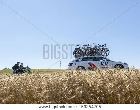 Saint-Quentin-FallavierFrance - July 16 2016: The technical car of IAM Cycling Team and an official bike driving in a wheat plain during the stage 14 of Tour de France 2016.