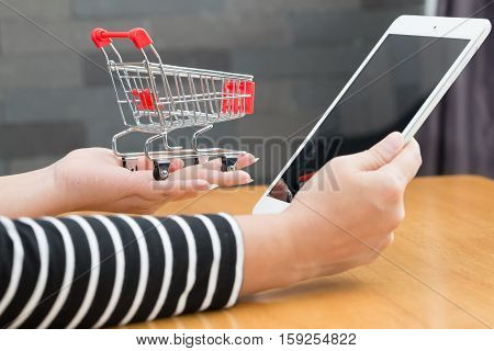 Online shopping concept Woman hand holding tablet and shopping cart