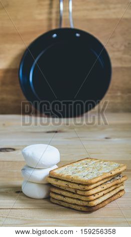 Pile of marshmallow and cracker on wooden table