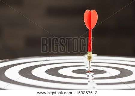 Target dart arrow hitting in the target center of dartboard