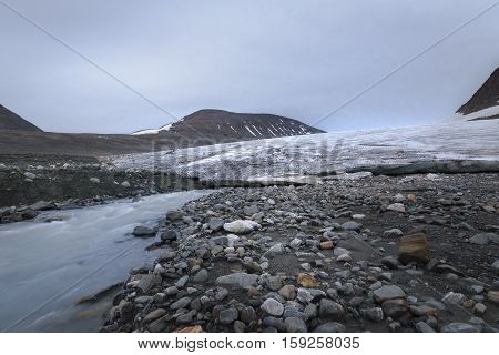 Big glacier in between mountain valley and river flowing fast with melted ice Sarek Sweden