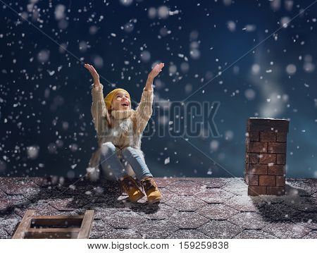 Happy child girl playing on a snowy winter walk. Little girl enjoys the game. Child girl sitting on the roof and looking at snowfall. Outdoor fun for winter vacation. Portrait kid on dark background.
