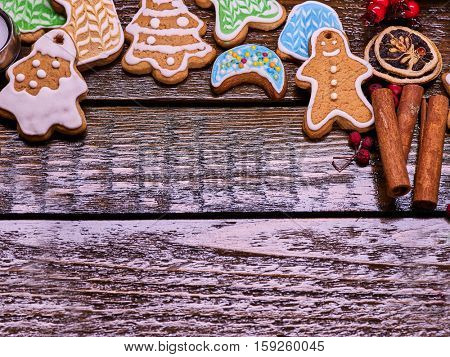 Christmas gingerbread cookies on woden table and candels. Background with copy spice