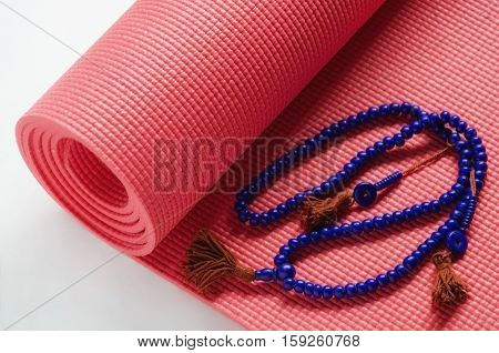 Pink yoga mat with violet mala bead necklace on white background. Yogi Essentials for practice and meditation.