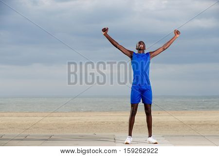 Fit Young Man On The Beach Celebrating Success