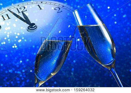 champagne flutes with golden bubbles make cheers on blue light bokeh background with vintage alarm clock is showing midday or midnight happy new year concept