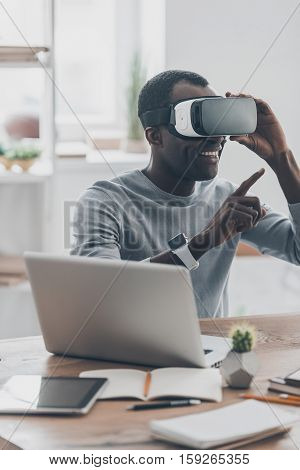Everything is so real! Handsome young African man in VR headset gesturing and smiling while sitting at the desk in creative office