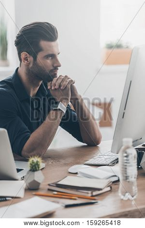 Waiting for inspiration. Handsome young man keeping hand to his face while sitting at his working place in home office