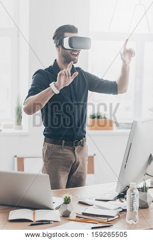 Everything is so real! Handsome young man in VR headset gesturing and smiling while standing in creative office