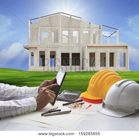 hand of architect working on computer tablet and house construction background