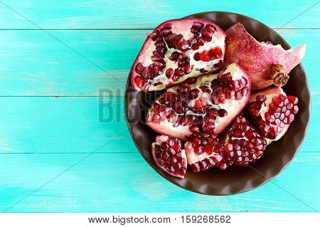 Ripe garnet have broken into pieces in a clay bowl. Juicy Asian fruit. The top view