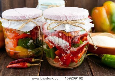 Marinated vegetables in a jar of glass: hot red and green peppers with sugar. Close-up.