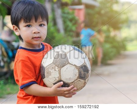 Asian kid in poor village playing with old soccer ball