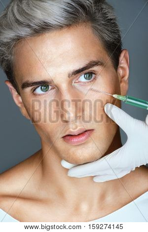 Beautiful man gets beauty facial injections. Aesthetic Cosmetology concept