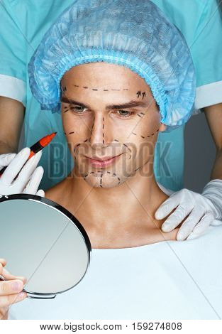 Smiling man looking in the mirror before cosmetic surgery. Doctor's hands with marker draws surgical lines on the face.