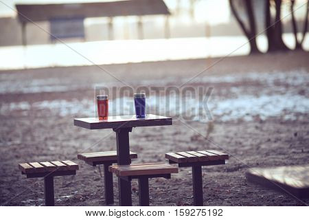 Two insulated coffee mugs on a wooden table.
