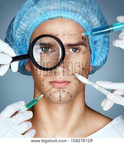 Man's face and beautician hands with syringes and scalpels near his face. Surgical mark lines on eyes nose cheek and jaw. Plastic Surgery concept