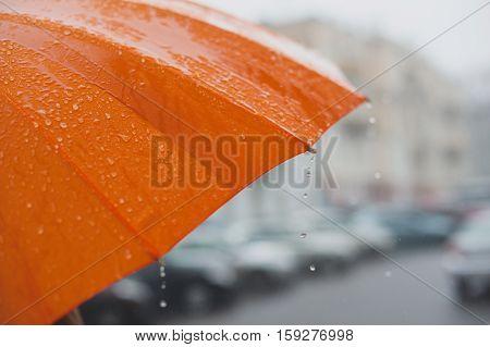 rain drops falling from a bright orange umbrella
