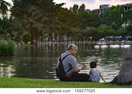 CHATUCHAK PARK, BANGKOK, THAILAND - NOVEMBER 27 : Grandpa and grandson relaxing in Chatuchak Park on the November 27, 2016 in Chatuchak Park, Bangkok.