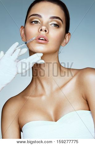 Beautiful woman face and beautician hands with syringe. Doctor makes cosmetic injection in the upper lip. Clean Beauty concept