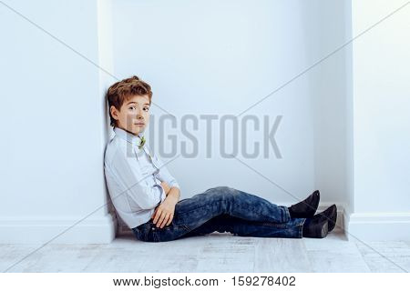 Fashion concept. Cute nine year old boy in elegant clothes posing in a room with classic white interior. Kid's fashion.
