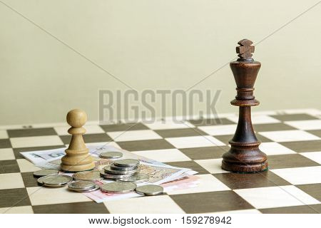 Chess king and pawn with money for a chessboard