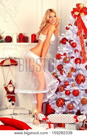 Congratulations on Christmas. Beautiful blonde near a Christmas tree at the bottom wedding lingerie