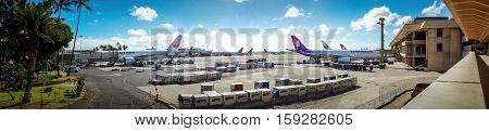 Hawaii, USA - Dec 22, 2015: Panorama of Honolulu International Airport, with various planes docked to their respective jetways.