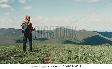 Hiker young man walking with trekking poles in the mountains