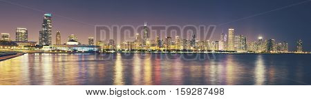 Retro toned panoramic picture of Chicago city skyline at night USA.