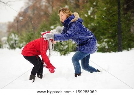Young woman and girl sculpts snowman. Woman and girl are dressed in bright and warm jackets. It is snowing. Woman carefully shakes off snow from girl's clothes. All earth is covered with fluffy snow.