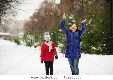Young woman with the daughter on walk in winter day. Woman and the girl are dressed in bright down-padded coats. It is snowing. Ground in the park is covered with snow. Mother throws snow up.